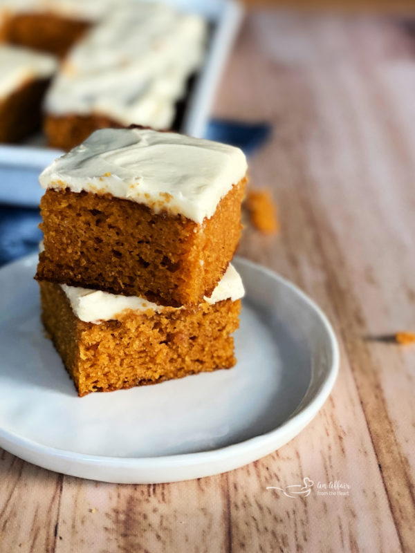 two carrot cake bars with cream cheese frosting on plate