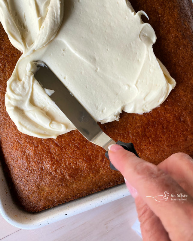 spreading cream cheese frosting on cooled carrot cake with baking tool