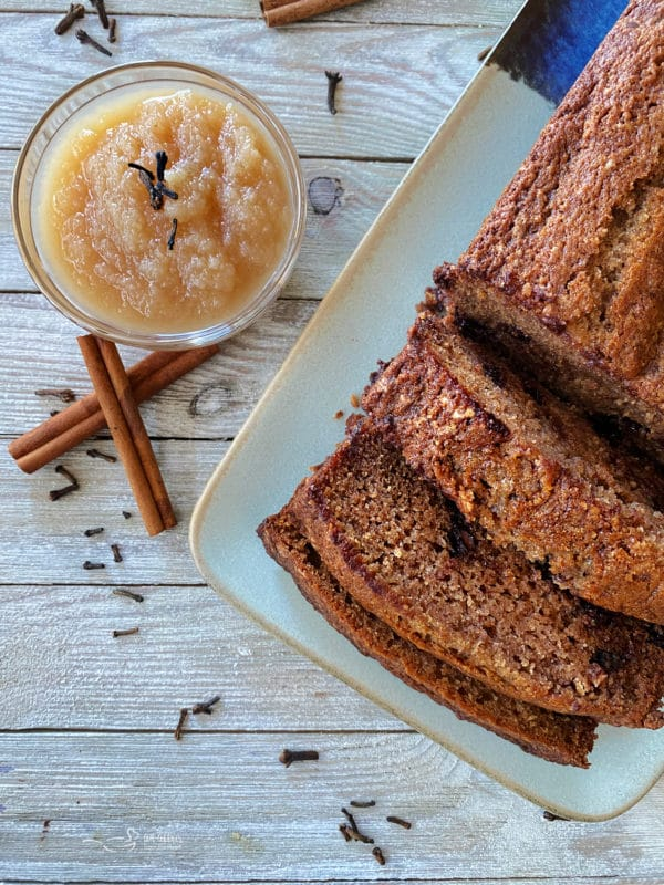 one loaf of applesauce bread on plate with bowl of applesauce and cinnamon sticks